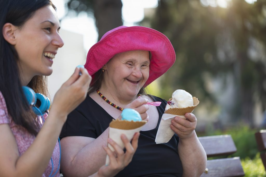 Woman with Down Syndrome and her friend eating ice cream and having fun in a park