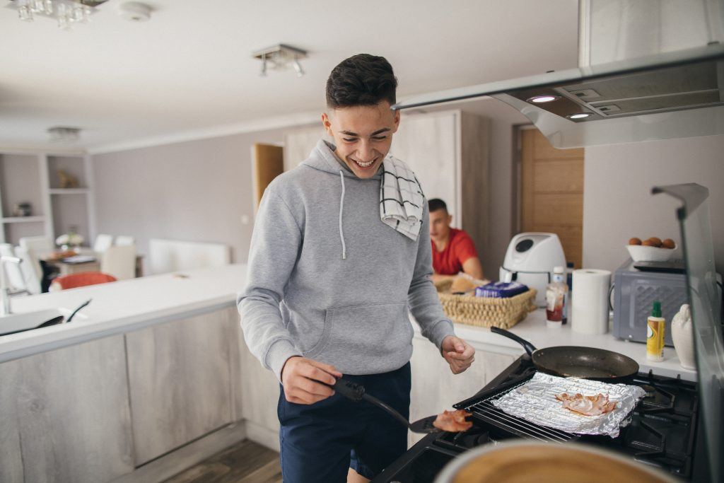 A teenage boy is frying bacon for a bacon sandwich. His friends are sitting at the kitchen island behind, waiting for their breakfast