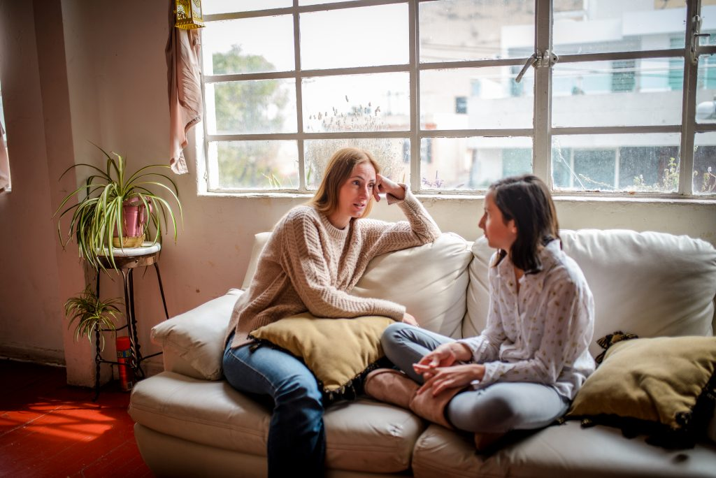 Mother and daughter at home having a talk at home on couch under window