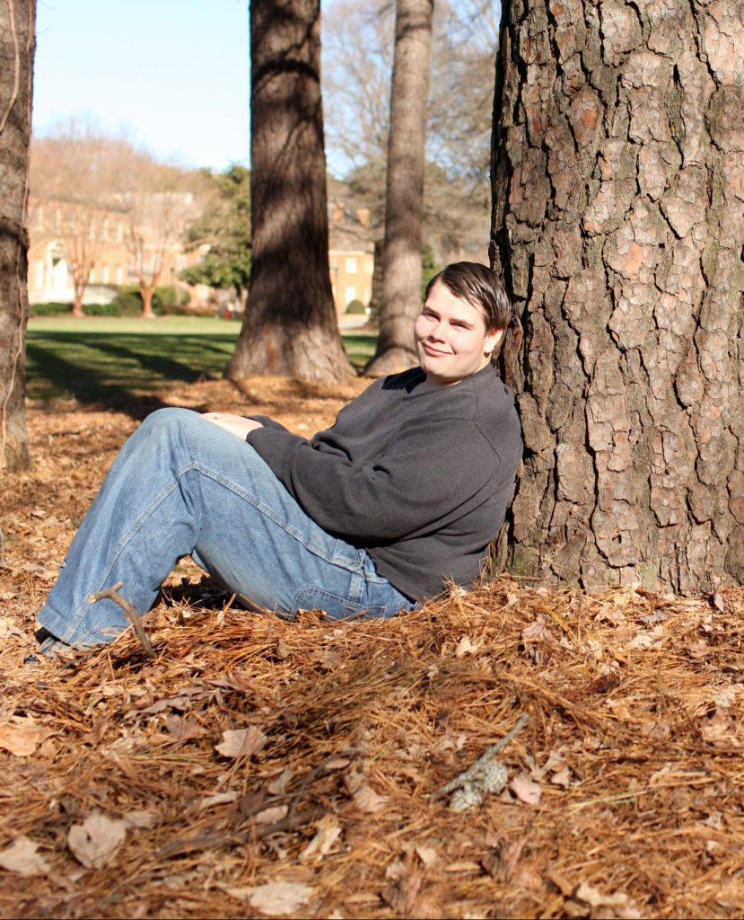 Man smiling leaning against tree