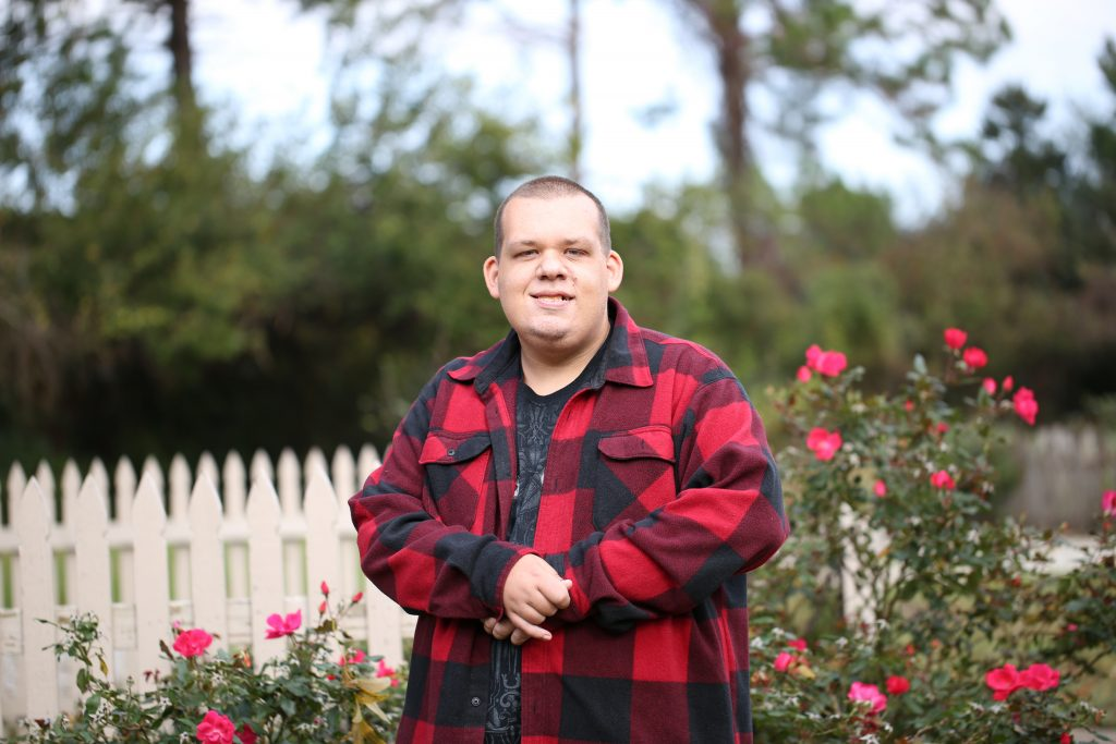 Young man with Autism posing for camera infront of rose bushes and white picket fence